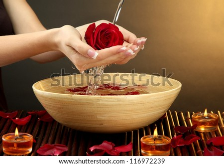 woman hands with wooden bowl of water with petals, on brown background - stock photo