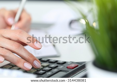 Woman hands working on calculator close up - stock photo