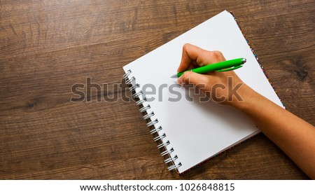 Woman hands writing in a notebook on a wooden background. with copy space. top view