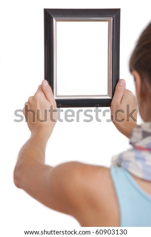 woman hanging photo frame - focus on hands - stock photo