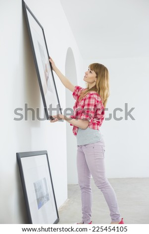 Woman hanging picture frame on wall in new house - stock photo