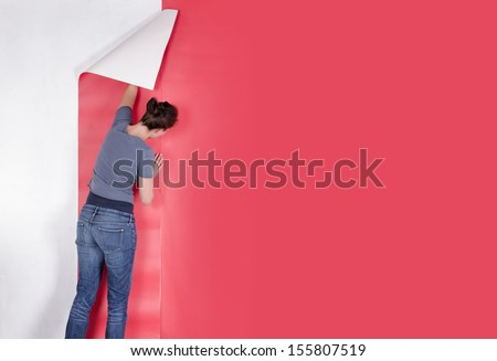 Woman hanging wallpaper. Decorating the wall - stock photo