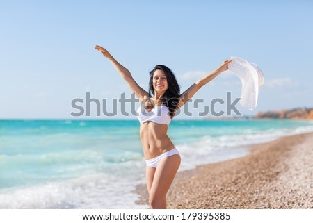 woman happy excited smile on beach ocean hold raised arms hands up, white hat and bikini swimsuit, young girl summer vacation holiday on sea sunny day blue sky