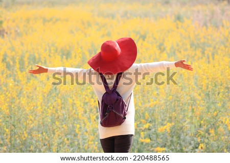 woman happy in free freedom pose with arms raised up towards the sky with smiling cheerful, elated expression of happiness. Beautiful girl in colorful of yellow blossom , flower forest outdoor  - stock photo