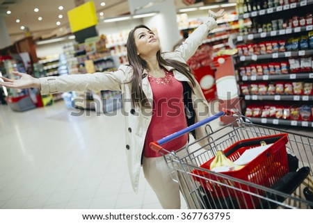 Woman happy when shopping in supermarket - stock photo