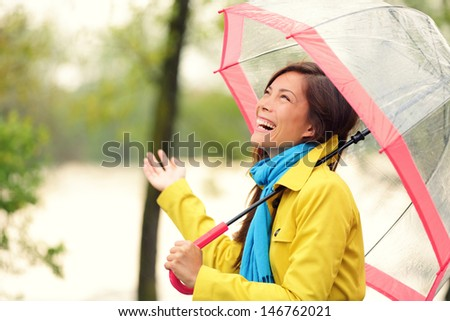 Woman happy with umbrella under the rain during Autumn forest walk. Girl enjoying rainy fall day looking up at sky smiling cheerful. Mixed race Caucasian / Asian chinese girl. - stock photo