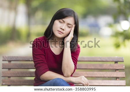 Woman Has Head Ache Sitting on Bench at Park - stock photo