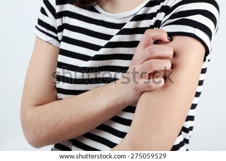 Woman has itch close up - stock photo