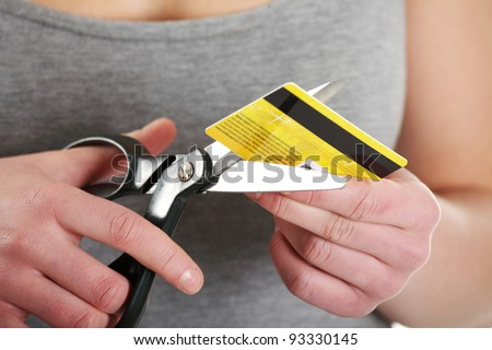 Woman has to destroy her credit card against a white background - stock photo
