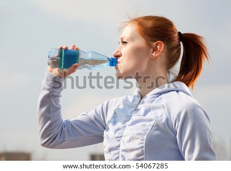woman have water from bottle against outdoor - stock photo