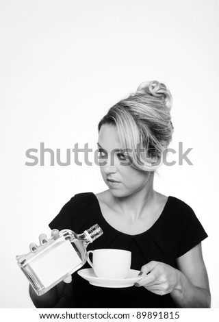 woman having a alcohol at work pouring it into her cup so no one will know - stock photo