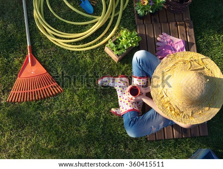 Woman having a coffee break while working in the garden - stock photo