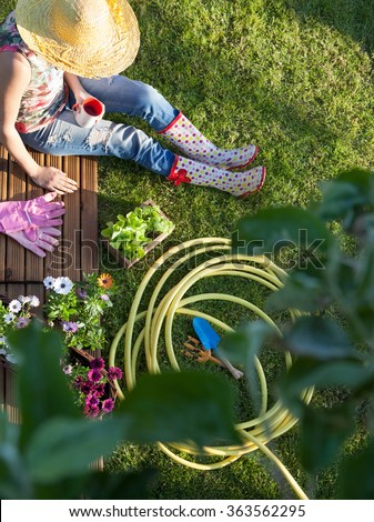 Woman having a coffee break while working in the garden, spring gardening concept - stock photo