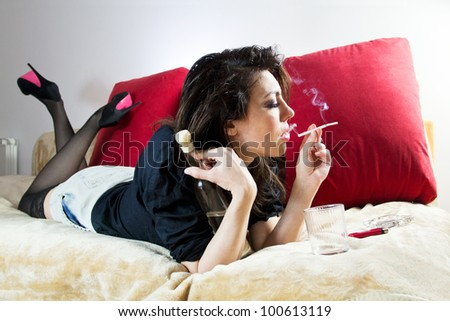 Woman having a drink and smoke. - stock photo