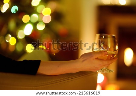 Woman having a drink by a fireplace in a cozy dark living room on Christmas eve - stock photo