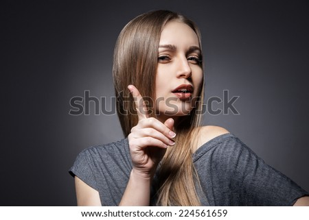 Woman having a good idea on dark grey background - stock photo