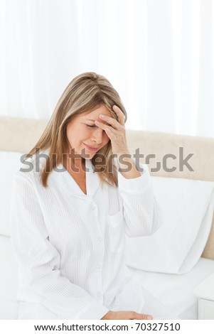 Woman having a headache on her bed - stock photo
