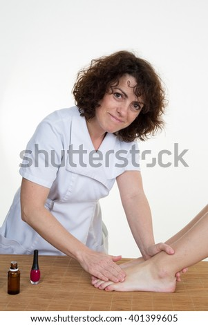 Woman having a pedicure treatment at a spa or beauty salon with the pedicurist massaging the soles of her feet  - stock photo