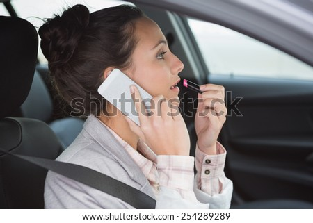 Woman having a phone call while putting on lipstick in her car - stock photo