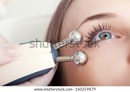 woman having a stimulating facial treatment from a therapist - stock photo