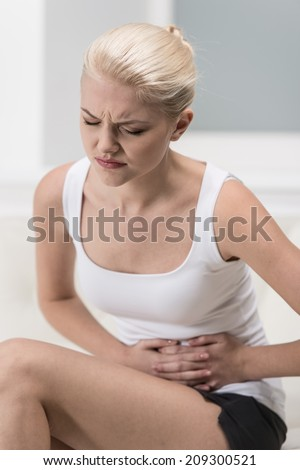 Woman having abdominal pain on sofa. blond girl with upset stomach or menstrual cramps  - stock photo