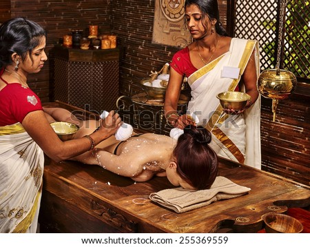 Woman having ayurvedic massage with pouch of rice. Passage to India - stock photo