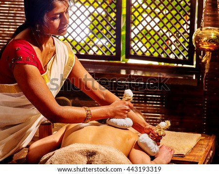 Woman having ayurvedic massage with pouch of rice. Passage to massage India - stock photo