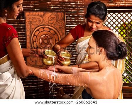 Woman having Ayurvedic spa treatment. Pouring milk. - stock photo