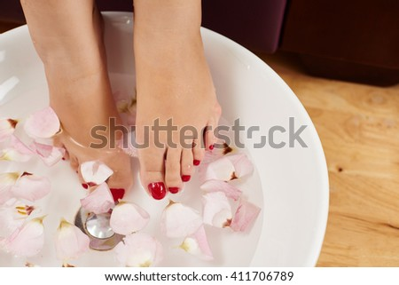 Woman having bath with rose petals for her feet - stock photo