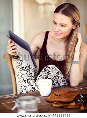 Woman having breakfast in a city cafe, drinking coffee and reading something on a tablet, modern life of a young successful people - stock photo
