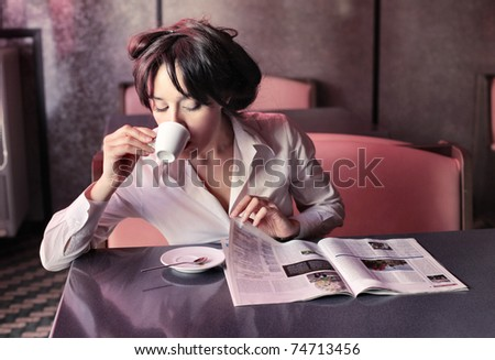 Woman having breakfast while reading a newspaper in a bar - stock photo