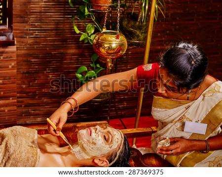 Woman having clay Indian facial mask at ayurveda spa. - stock photo