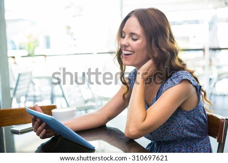 Woman having coffee and using her tablet in a coffee shop