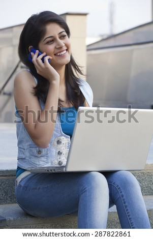 Woman having conversation on mobile phone in college campus - stock photo