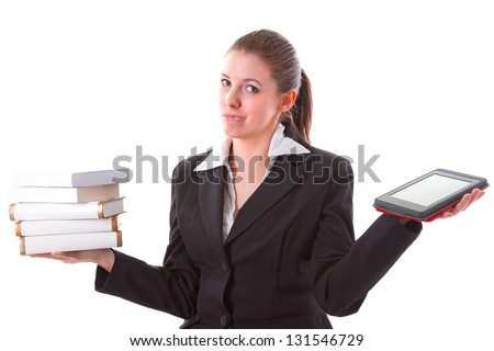 Woman having dilemma between stack of books and ebook reader - stock photo