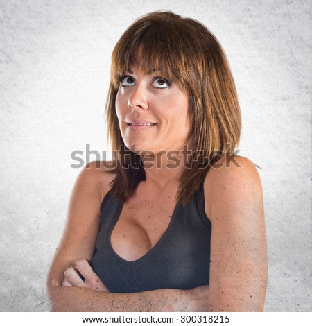 Woman having doubts over grey background - stock photo