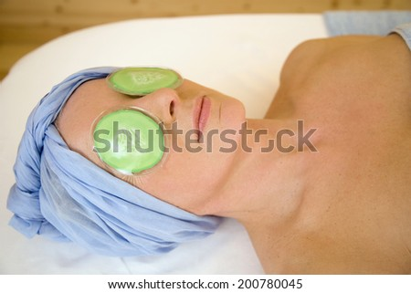 Woman having eye mask on relaxing on massage bench