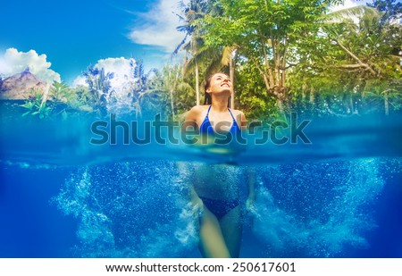woman having fun in the pool - view half way from under the water - stock photo