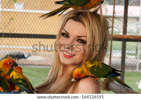 Woman Having Fun Playing With Parrot - stock photo
