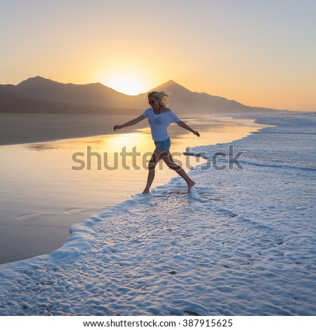 Woman having fun runing from waves on solitary sandy beach in sunset. Waves sweeping away her traces in sand. Beach, travel, concept. Copy space.  - stock photo