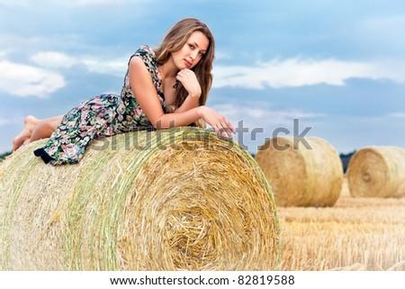 Woman having fun sitting on hay bale - stock photo