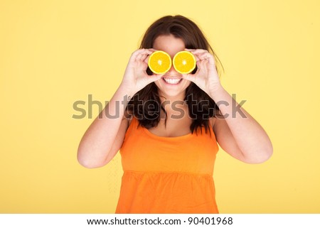 Woman Having Fun With Oranges holding two slices over her eyes .