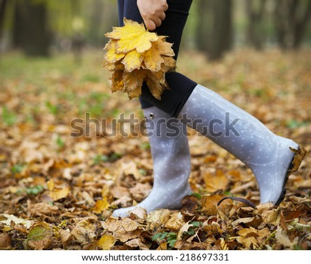 Woman having fun with yellow maple leaves in the autumn park - stock photo