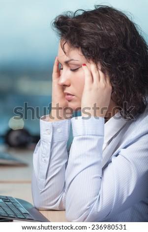 Woman having head ache at work - stock photo