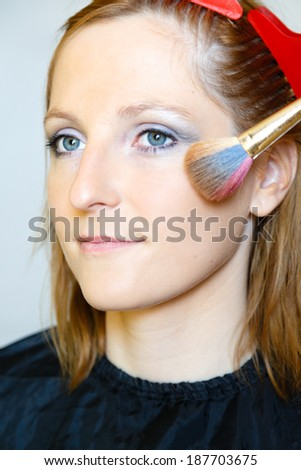 Woman having her hair and make up done for photo shooting