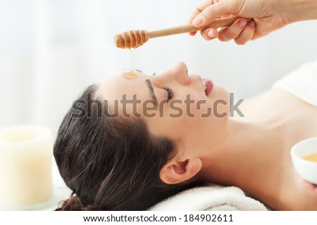 Woman having honey facial massage at spa salon - stock photo