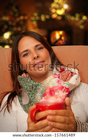 Woman having Hot Drink during Christmas night seating at her home waiting for presents - stock photo