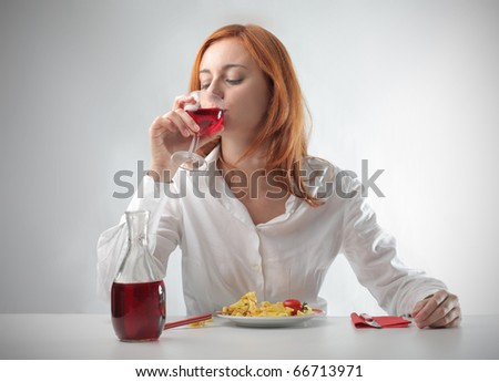 Woman having lunch and drinking a glass of red wine - stock photo