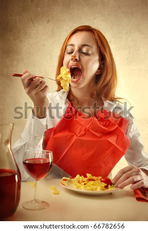 Woman having lunch with tagliatelle and red wine - stock photo