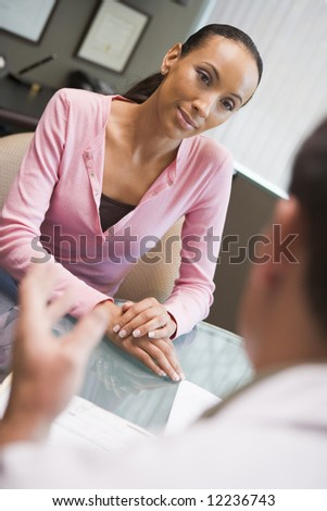 Woman having meeting with doctor in IVF clinic sitting at desk - stock photo